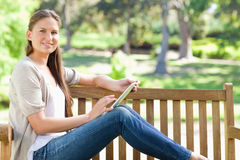 Side view of a smiling woman using a tablet computer on a park b Stock Images
