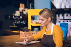 Cheerful barista making notes in confectionary shop. Side view smiling worker writing information while locating at counter in modern cafe. Labor concept Stock Photo