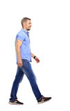 Side view of a smiling young casual man walking , on white backg Royalty Free Stock Photos