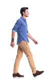 Side view of a smiling young casual man walking Stock Images