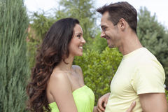 Side view of smiling young couple looking at each other in park Royalty Free Stock Image