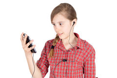 Side View of Smiling Young Girl With Earbuds  Listening to Music on Her Cellphone Isolated on White Royalty Free Stock Images