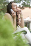 Side view of smiling young woman using mobile phone in park Stock Images