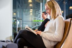 Side View Of Smiling Woman Reading Book At Airport. Side view of smiling young women reading book with men in background at airport waiting area stock photography