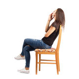 Side view of smoking casual woman sitting on chair Stock Photography