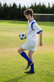 Side view of soccer player playing with ball. On field Stock Images