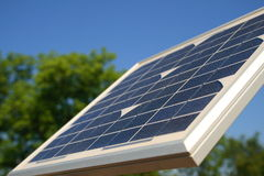 Side View Solar. Side view of a solar panel with a background of vivid green trees and a perfect blue sky Royalty Free Stock Photos