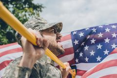 Side view of soldier pulling himself up on crossbar with american flag. On backdrop stock photo