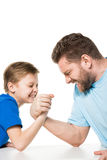 Side view of son with father arm wrestling. Isolated on white Stock Photos