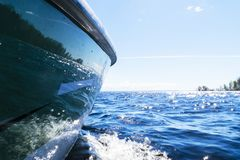 Side view Speeding fishing motor boat with drops of water. Blue ocean sea water wave reflections with fast fishing yacht. Motor bo. At in the blue ocean. Ocean stock photos