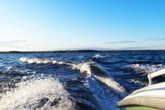Side view Speeding fishing motor boat with drops of water. Blue ocean sea water wave reflections with fast fishing yacht. Motor bo. At in the blue ocean. Ocean royalty free stock photo
