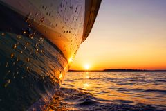 Side view Speeding fishing motor boat with drops of water. Blue ocean sea water wave reflections at the sunset. Motor boat in the. Blue ocean. Ocean yacht royalty free stock photo