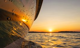 Side view Speeding fishing motor boat with drops of water. Blue ocean sea water wave reflections at the sunset. Motor boat in the. Blue ocean. Ocean yacht stock photos