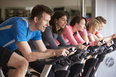Side view of a spinning class on exercise bikes at a gym royalty free stock photography