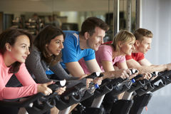 Side view of a spinning class on exercise bikes at a gym Royalty Free Stock Photo