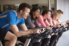 Side view of a spinning class on exercise bikes at a gym Royalty Free Stock Images