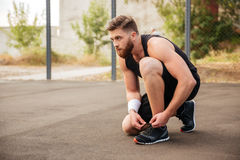 Side view of a sports man athlete ties his shoelaces Stock Images