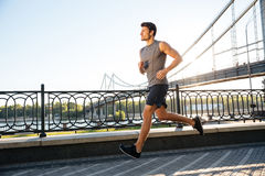 Side view of sportsman running along bridge at sunset light Royalty Free Stock Photo
