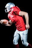 Side view of sportsman running while playing American football Royalty Free Stock Images