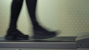 Side view of the sportsman`s feet walking on a treadmill stock video