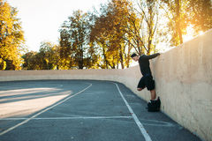 Side view on sportsman stretching near wall. Side view on sportsman stretching arms near wall, free space. Young man doing sport exercises on open air stadium Stock Image