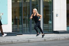 Side view of sporty woman running fast in minimalist urban environment Royalty Free Stock Photo