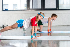 Side view of sporty boy and girl in sportswear doing push ups in gym Stock Photo