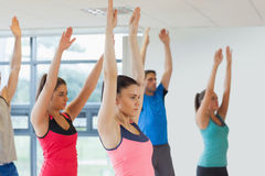 Side view of sporty people raising hands at yoga class Royalty Free Stock Photo