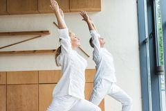 Side view of sporty senior couple performing warrior pose while practicing yoga royalty free stock images