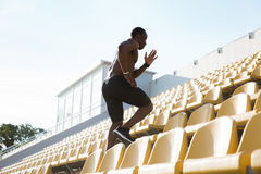 Side view of a sporty young man runner on stadium. Side view of a sporty young man runner on a stadium running upstairs Royalty Free Stock Photos