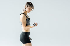 Side view of sporty young woman exercising with dumbbells Royalty Free Stock Photos