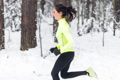 Side view of sporty young woman running in morning Winter street training workout. Side view of sporty young woman running in morning Winter street training Stock Images