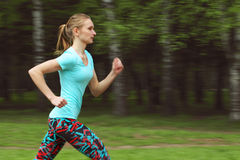 Side view of sporty young woman running in park Stock Photography