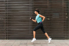 Side view of sporty young woman running on a sidewalk. Royalty Free Stock Images