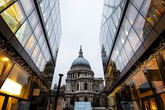 St.Paul's Cathedral reflected on glass office building in Lond. Side view of St.Paul's Cathedral in London. Built after The Great Fire Of London of 1666, it` Royalty Free Stock Image