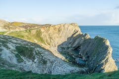 Side view of Stair Hole cove in Dorset, southern England. Showing folded limestone strata rock formations and the English Channel beyond Stock Images