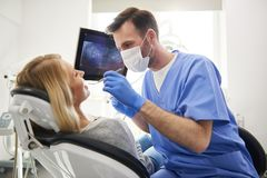 Stomatologist doing his work in dentist`s clinic. Side view of stomatologist doing his work in dentist`s clinic stock photo