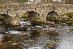 A side view of the stone Pack Horse bridge over the East Dart River in Dartmoor National Park, England. With nobody crossing the bridge stock image