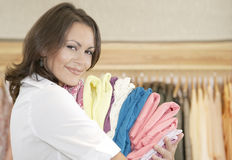Side View of a Store Attendant Holding Pile of Clothes Royalty Free Stock Photography