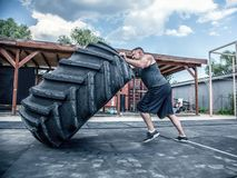 Side view of strong muscular fitness man moving large tire in street gym. Concept lifting, workout training royalty free stock images