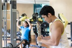 Strong young man exercising triceps pushdown at the rope cable m. Side view of a strong young men exercising triceps pushdown at the rope cable machine in a royalty free stock image