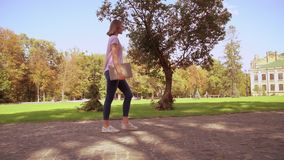 Blonde woman holds computer walks in campus area. Side view student holding laptop. girl with blond hair wearing pink t-shirt and jeans stroll in park on the stock footage