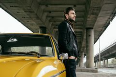 Side view of stylish man. Standing near yellow retro car and looking away royalty free stock photos