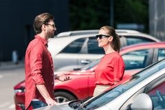 Side view of stylish man. In sunglasses talking to girlfriend near car stock image