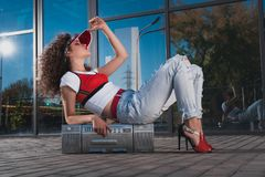 Stylish woman lying on boombox. Side view of stylish woman in jeans lying on boombox stock images