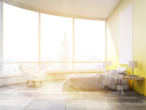 Side view of sunlit bedroom with yellow walls in New York Royalty Free Stock Images