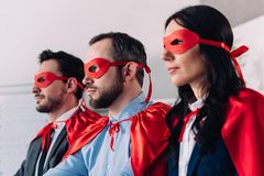 side view of super businesspeople in masks and capes looking away royalty free stock photos