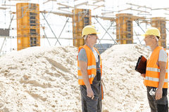 Side view of supervisors discussing at construction site Stock Photos