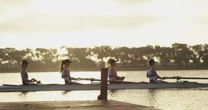 Female rowing team training on a river. Side view of a team of four young adult Caucasian women rowing in a racing shell on a river stock footage
