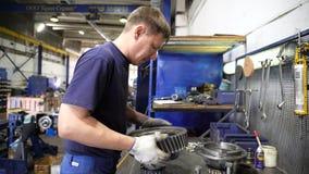 Side view technician checks and assembles truck part